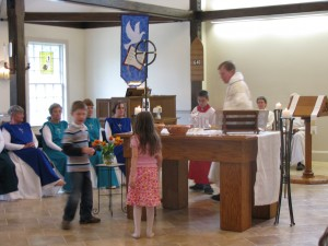 Children of the congregation bring the gifts of bread and wine to the Altar.