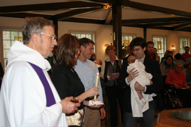 Bishop Arthur Walmsley prepares to chrismate a newly baptized infant.