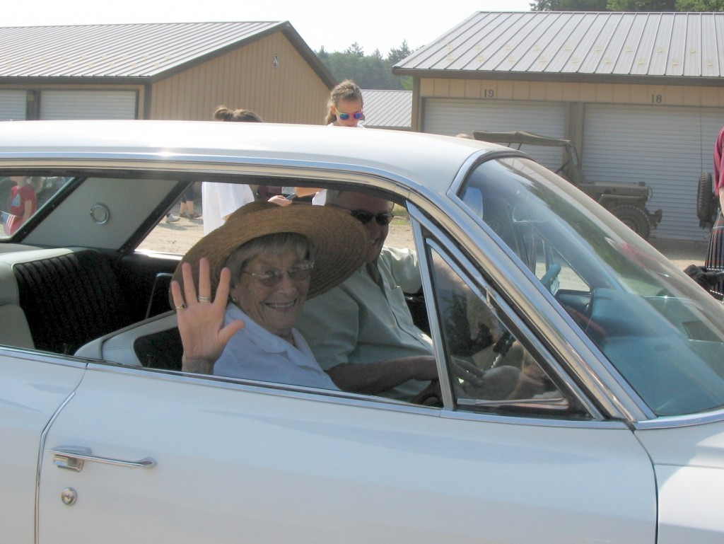 """Queen Alice"" waves from the seat of Thom Thomas's 1964 Cadillac."