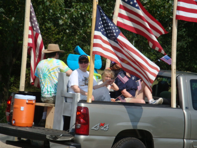 Will Townsend's flag-decked truck carried riders on an old church pew.