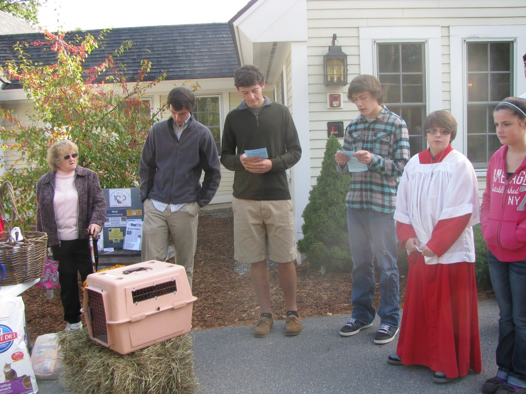 Ben Harrington, Connor Houghton and Ryan Compagna read stories of St. Francis and the animals as Henry and Henriette the chickens await their blessing in their box.